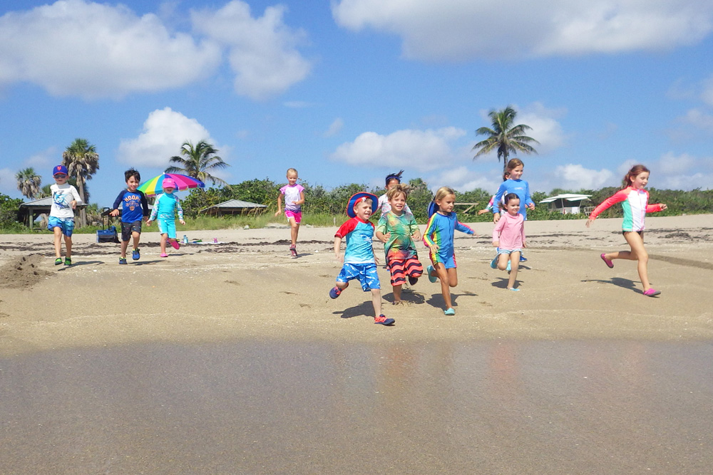 children rushing towards the beach